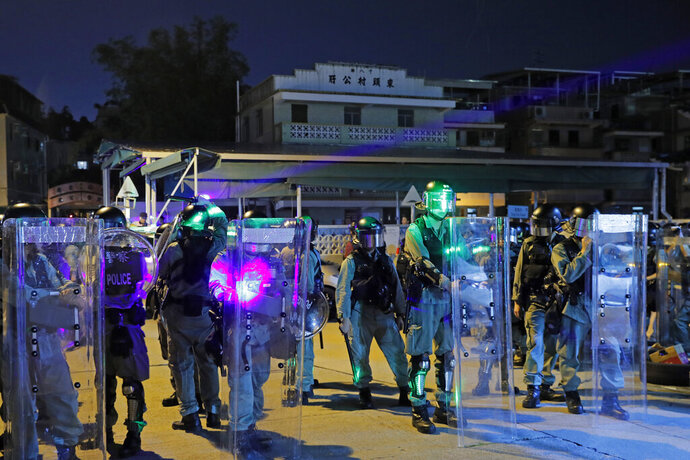 In this Wednesday, Aug. 21, 2019 file photo, riot police are illuminated by laser pointers from protesters during a protest at the Yuen Long MTR station in Hong Kong. A Hong Kong lawmaker has voiced concern the conviction of a teenager for carrying a laser pointer could pave the way for more prosecutions against anti-government protesters in the semi-autonomous Chinese territory. Local broadcaster RTHK says a court Thursday found a 16-year-old male student guilty of possessing the laser pointer and a modified umbrella — deemed to be offensive weapons. He was detained Sept. 21 near the site of a planned protest for democratic reforms. (AP Photo/Kin Cheung, file)
