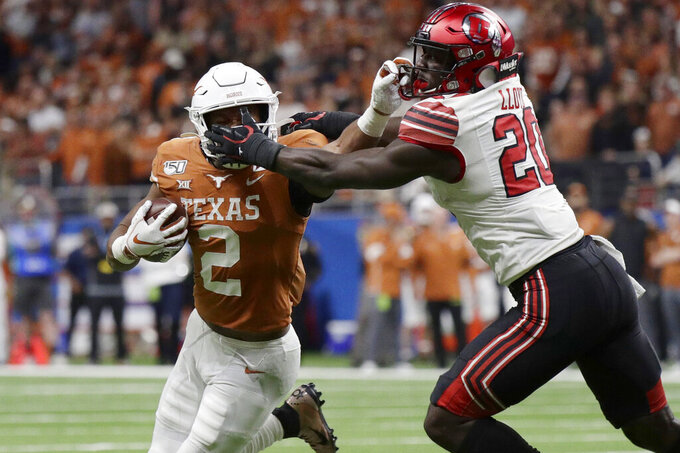 Texas running back Roschon Johnson (2) has his face mask grabbed by Utah linebacker Devin Lloyd (20) during the second half of the Alamo Bowl NCAA college football game in San Antonio, Tuesday, Dec. 31, 2019. (AP Photo/Eric Gay)