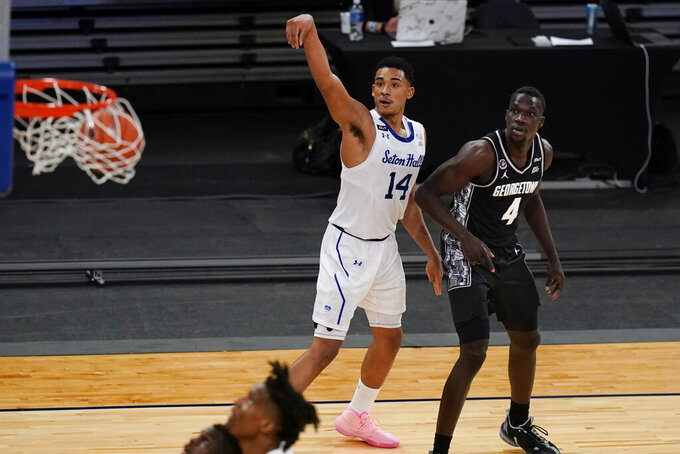 Georgetown's Chudier Bile (4) and Seton Hall's Jared Rhoden (14) watch Rhoden's 3-point basket during the second half of an NCAA college basketball game in the semifinals in the Big East men's tournament Friday, March 12, 2021, in New York. (AP Photo/Frank Franklin II)