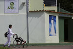 In this Jan. 4, 2019 photo, a woman pushes a wheelchair past the Norberto Kist hostel, promoting Brazilian spiritual healer Joao Teixeira de Faria, who goes by the name