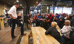 Former Texas congressman Beto O'Rourke rests his foot on a picnic table as he listens to a question during a campaign stop at a brewery in Conway, N.H., Wednesday, March 20, 2019. O'Rourke announced last week that he'll seek the 2020 Democratic presidential nomination. (AP Photo/Charles Krupa)
