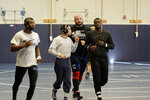 In this March 2, 2020, photo, former Nebraska football player Tanner Farmer and current wrestler for Concordia University, second from right, jogs with teammates during practice in Seward, Neb. A year ago Farmer was thought to be on the rise as an NFL draft prospect. He had started three years on Nebraska's offensive line and turned in a stellar performance at the Cornhuskers' pro day. It turned out he went undrafted, so he took a volunteer assistant's job with the Concordia football team and then, quite by accident, discovered he had one semester of eligibility to compete in another sport in the National Association of Intercollegiate Athletics. He chose wrestling. (AP Photo/Nati Harnik)