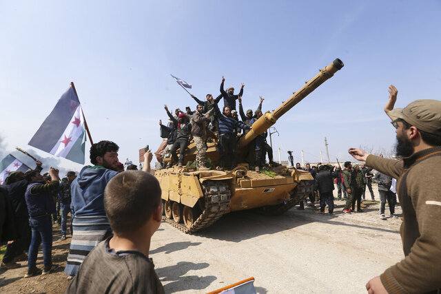 Syrians climb on a Turkish tank in Neyrab, Sunday, March 15, 2020 as they protest agreement on joint Turkish and Russian patrols in northwest Syria. Patrols on the M4 highway, which runs east-west through Idlib province, are part of a cease-fire agreed between Turkey and Russia after an escalation in fighting that saw the Turkish military in direct conflict with Syrian government troops.( (AP Photo/Ghaith Alsayed)
