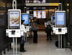 FILE - This Aug. 8, 2018, file photo shows electronic menus at the McDonald's flagship restaurant in Chicago. In a very limited test in Canada, McDonald's said Thursday, Sept. 26, 2019, that it's introducing the PLT, or the plant, lettuce and tomato burger. It will be available for 12 weeks in 28 restaurants in Southwestern Ontario by the end of the month. (AP Photo/Nam Y. Huh, File)