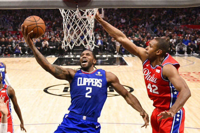 FILE - In this March 1, 2020, file photo, Los Angeles Clippers forward Kawhi Leonard, left, shoots as Philadelphia 76ers forward Al Horford defends during the second half of an NBA basketball game in Los Angeles. (AP Photo/Mark J. Terrill, File)