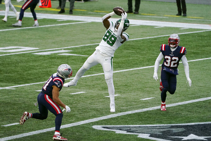 New York Jets tight end Chris Herndon, center, catches a touchdown pass between New England Patriots defensives backs Myles Bryant, left, and Devin McCourty, right, in the first half of an NFL football game, Sunday, Jan. 3, 2021, in Foxborough, Mass. (AP Photo/Elise Amendola)