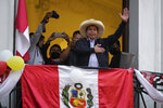Presidential candidate Pedro Castillo waves to supporters celebrating partial election results that show him leading over Keiko Fujimori, at his campaign headquarters in Lima, Peru, Monday, June 7, 2021, the day after a runoff election. (AP Photo/Martin Mejia)