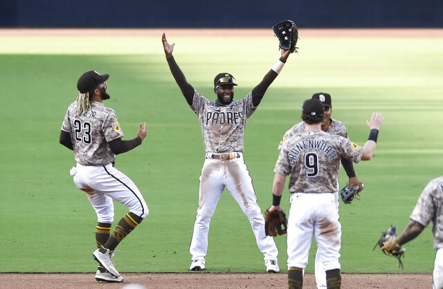 San Diego Padres' Fernando Tatis Jr. (23), Jurickson Profar (10), and Jake Cronenworth (9) celebrate after the Padres beat the Seattle Mariners in a baseball game Sunday, Sept. 20, 2020, in San Diego. The Padres clinched a spot in the playoffs. (AP Photo/Denis Poroy)