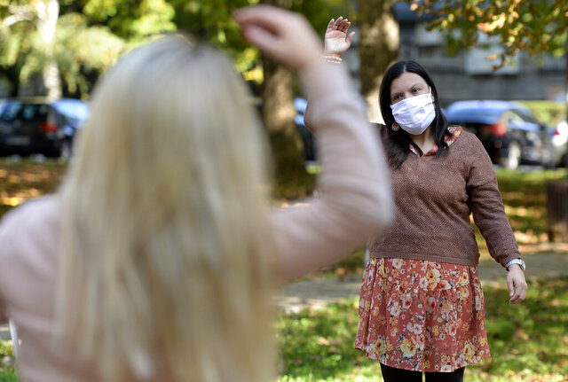 Women exercise during a therapy session in a park in Sarajevo, Bosnia Monday, Oct. 26, 2020. As coronavirus cases surge in Bosnia, the pandemic is heaping new trouble on an impoverished nation that has never recovered economically or psychologically from a war in the 1990s. Bosnian health authorities estimate that nearly half of the Balkan nation's nearly 3.5 million people have suffered some degree of trauma resulting from the war. (AP Photo/Kemal Softic)