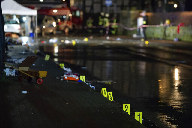 Investigators' markings are seen near the car that drove into a crowd of people during a carnival procession in Volkmarsen, Germany, Monday, Feb. 24, 2020. A man intentionally drove a car into a crowd of people at a Carnival parade in a small town in central Germany, injuring dozens of people including children, officials said Monday. Prosecutors said the driver, a 29-year-old local man, was arrested at the scene of the incident in Volkmarsen, about 280 kilometers (175 miles) southwest of Berlin. (Swen Pfortner/dpa via AP)