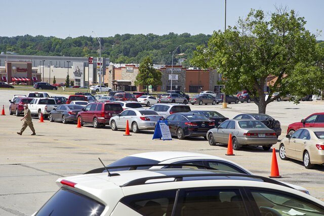 A double line of cars snakes around a parking lot at a coronavirus testing site in Omaha, Neb., Wednesday, July 8, 2020. (AP Photo/Nati Harnik)