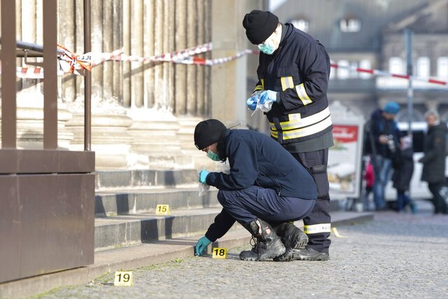 Police officers work behind a caution tape at the Schinkelwache building in Dresden Monday, Nov. 25, 2019. Authorities in Germany say thieves have carried out a brazen heist at Dresden's Green Vault, one of the world's oldest museum containing priceless treasures from around the world. (Sebastian Kahnert/dpa via AP)