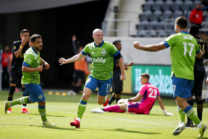 Seattle Sounders defender Brad Smith (11) celebrates his goal between midfielder Cristian Roldan (7) and forward Will Bruin (17) during the second half of an MLS soccer match against the Los Angeles FC, Saturday, April 24, 2021, in Los Angeles. The game ended in a 1-1 draw. (AP Photo/Ringo H.W. Chiu)