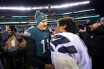 Philadelphia Eagles' Josh McCown, left, meets with Seattle Seahawks' Russell Wilson after an NFL wild-card playoff football game, Sunday, Jan. 5, 2020, in Philadelphia. Seattle won 17-9. (AP Photo/Chris Szagola)