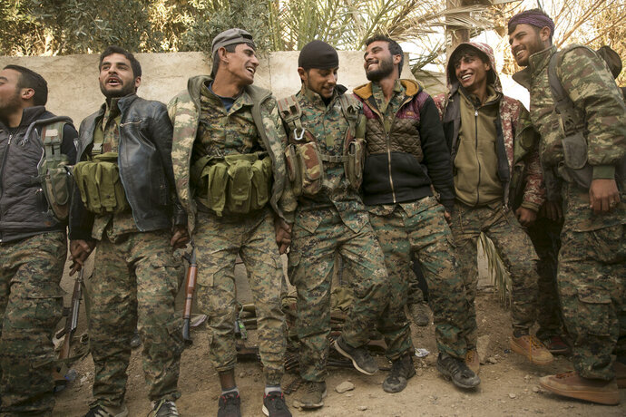 U.S.-backed Syrian Democratic Forces (SDF) fighters celebrate their territorial gains over Islamic State militants in Baghouz, Syria, move to a camp Tuesday, March 19, 2019.  On Tuesday, a spokesman for U.S.-backed forces fighting IS in Syria says his fighters are in control of an encampment in the village of Baghouz where IS militants have been besieged for months. (AP Photo/Maya Alleruzzo)