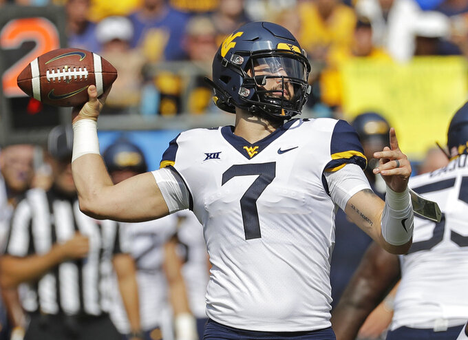 West Virginia's Will Grier (7) looks to pass against Tennessee in the first half of an NCAA college football game in Charlotte, N.C., Saturday, Sept. 1, 2018. (AP Photo/Chuck Burton)