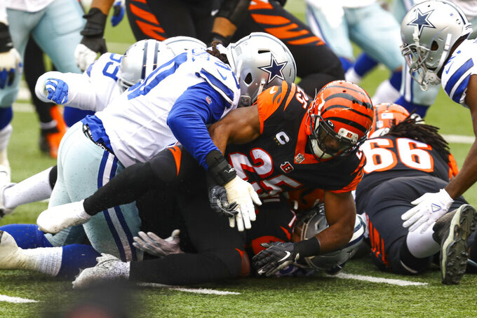 Cincinnati Bengals running back Giovani Bernard (25) fumbles the ball as he tackled by Dallas Cowboys defensive end DeMarcus Lawrence (90) in the first half of an NFL football game in Cincinnati, Sunday, Dec. 13, 2020. (AP Photo/Aaron Doster)