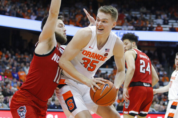 Syracuse's Buddy Boeheim, right, drives to the basket against North Carolina State's Braxton Beverly, left, in the second half of an NCAA college basketball game in Syracuse, N.Y., Tuesday, Feb. 11, 2020. North Carolina State won 79-74. (AP Photo/Nick Lisi)
