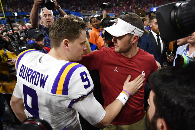 LSU quarterback Joe Burrow (9) speaks with Oklahoma head coach Lincoln Riley after the Peach Bowl NCAA semifinal college football playoff game, Saturday, Dec. 28, 2019, in Atlanta. LSU won 63-28. (AP Photo/Danny Karnik)