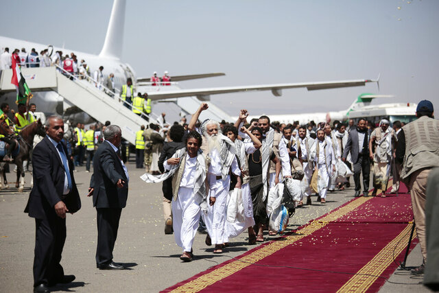 Yemeni prisoners chant slogans during their arrival after being released by the Saudi-led coalition at the airport in Sanaa, Yemen, Friday, Oct. 16, 2020. Yemen's warring sides completed a major, U.N.-brokered prisoner swap on Friday, officials said, a development that could revive the country's stalled peace process after more than five years of grinding conflict. (AP Photo/Hani Mohammed)