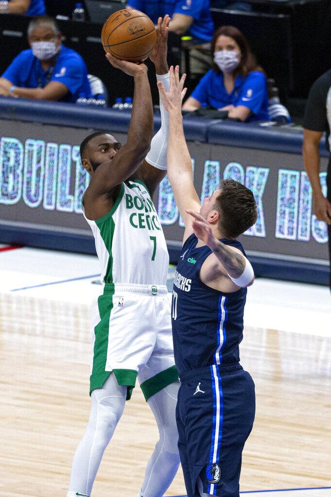 Boston Celtics guard Jaylen Brown (7) shoots as Dallas Mavericks guard Luka Doncic (77) defends during the first half of an NBA basketball game in Dallas, Tuesday, Feb. 23, 2021. (AP Photo/Sam Hodde)