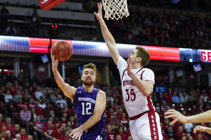 Northwestern's Pat Spencer (12) passes as Wisconsin's Nate Reuvers (35) defends during the first half of an NCAA college basketball game Wednesday, March 4, 2020, in Madison, Wis. (AP Photo/Andy Manis)