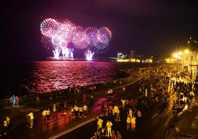 People walk along the malecon watching the fireworks as part of the celebration of the 500 years of the city in Havana, Cuba, Friday, Nov. 15, 2019. Havana celebrate its 500th anniversary on Saturday, a milestone event which has sparked reflection and anticipation in the country, as it faces an increasingly hostile US Administration and serious economic challenges. (AP Photo/Ramon Espinosa)