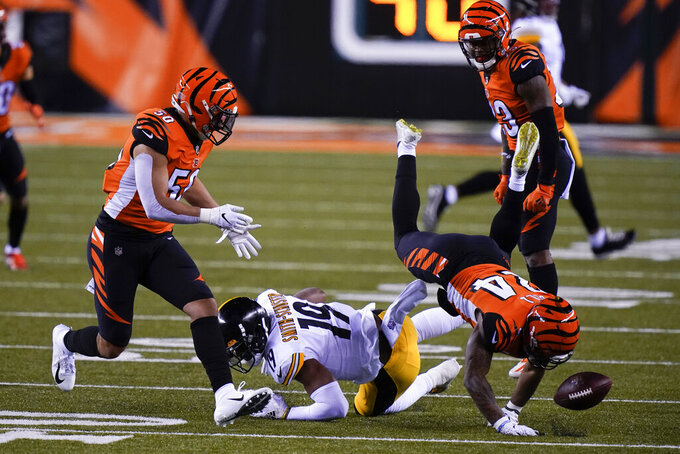 Cincinnati Bengals' Vonn Bell (24) and Jordan Evans (50) look to recover a fumble by Pittsburgh Steelers' JuJu Smith-Schuster (19) during the first half of an NFL football game, Monday, Dec. 21, 2020, in Cincinnati. (AP Photo/Bryan Woolston)
