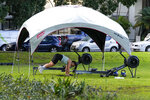 A woman workout in a park in the eastern suburbs of Sydney Tuesday, Sept. 14, 2021. Personal trainers have turned a waterfront park at Sydney's Rushcutters Bay into an outdoor gym to get around pandemic lockdown restrictions. (AP Photo/Mark Baker)