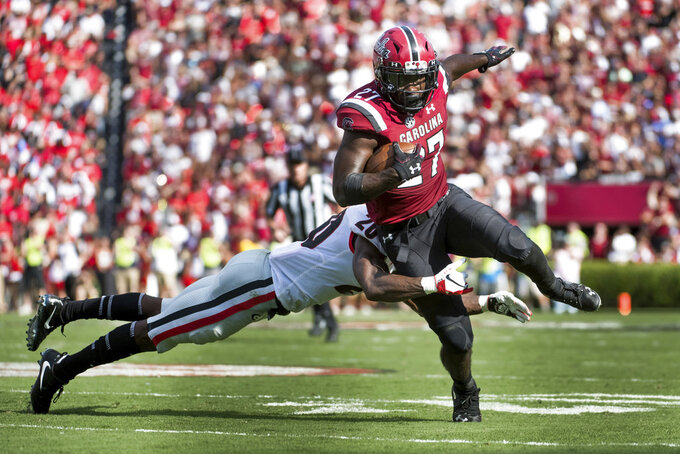 South Carolina running back Ty'Son Williams (27) runs with the ball against Georgia defensive back J.R. Reed (20) during the first half of an NCAA college football game Saturday, Sept. 8, 2018, in Columbia, S.C. (AP Photo/Sean Rayford)