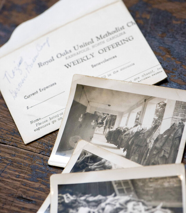 In this Oct. 10, 2020 photo, photographs showing Nazi concentration Camp at Dachau the day after it was liberated by allied forces are displayed at the Rowan Museum in Salisbury, N.C,  The photos were found in the belongings of James Bruton, the late grandfather of Rowan County Fire Marshal Deborah Horne. (Jon C. Lakey/The Salisbury Post via AP)