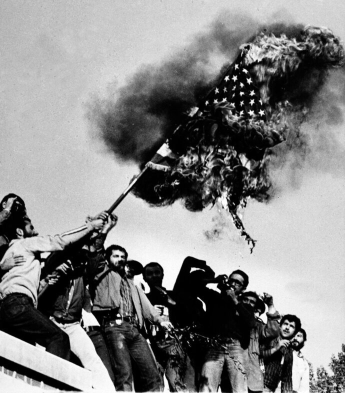 FILE - In this Nov. 9, 1979 file photo, demonstrators burn an American flag atop the wall of the U.S. Embassy in Tehran, Iran, where students have been holding American hostages. Nov. 4, 2019, will mark the 40th anniversary of the start of the 444-day hostage crisis that soured relations between the U.S. and the Islamic Republic for decades to come. (AP Photo/Thierry Campion, File)