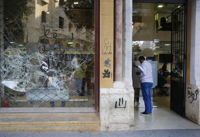 A client enters a bank with a front window shattered during anti-government protests in Beirut, Lebanon, Friday, Nov. 1, 2019. Lebanon's private banks have reopened after a two-week closure because of the protests. The Arabic words on the damaged window read:
