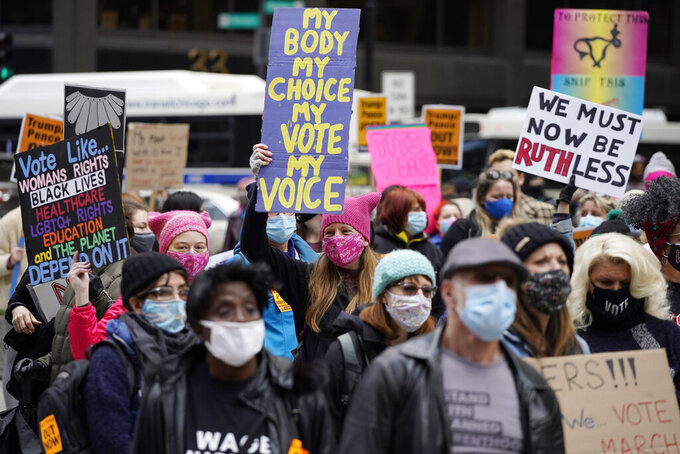 People march during the Women's March in downtown Chicago, Saturday, Oct. 17, 2020.  Dozens of Women's March rallies were planned from New York to San Francisco to signal opposition to President Donald Trump and his policies, including the push to fill the seat of late Supreme Court Justice Ruth Bader Ginsburg before Election Day. (AP Photo/Nam Y. Huh)