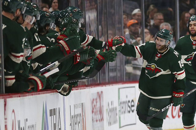 Minnesota Wild's Luke Kunin high fives teammates on the bench after he scored a goal against the Calgary Flames in the second period of an NHL hockey game Monday Dec. 23, 2019, in St. Paul, Minn. (AP Photo/Stacy Bengs)