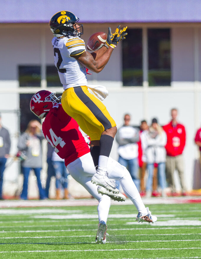 Iowa wide receiver Brandon Smith (12) catches a pass as he's defended by Indiana defensive back Andre Brown Jr. (14) during the first half of an NCAA college football game Saturday, Oct. 13, 2018, in Bloomington, Ind. (AP Photo/Doug McSchooler)