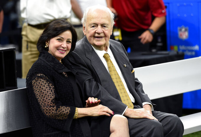 FILE - In this Sept. 17, 2017, file photo, New Orleans Saints owner Tom Benson sits on the sideline with his wife, Gayle Benson, before an NFL football game in New Orleans. An Associated Press review of public tax documents found that the Bensons' foundation has given at least $62 million to the Archdiocese of New Orleans and other Catholic causes over the past dozen years, including gifts to schools, universities, charities and individual parishes. (AP Photo/Bill Feig, File)