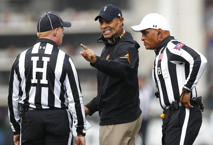 Arizona State head coach Herm Edwards, center, confers with head linesman Bob Day, left, and referee Javarro Edwards in the first half of an NCAA college football game against Colorado Saturday, Oct. 6, 2018, in Boulder, Colo. (AP Photo/David Zalubowski)