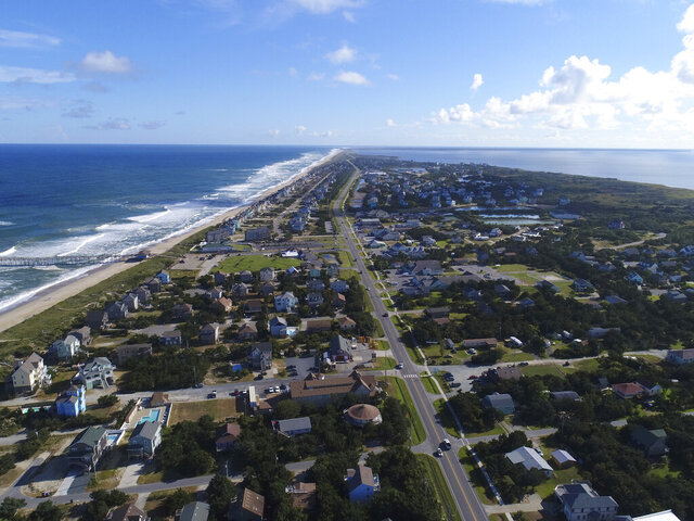 FILE - In this Monday, Sept. 10, 2018, file photo provided by DroneBase, waves crash along Avon, N.C., in Dare County, in the Outer Banks. Three counties on North Carolina's tourist-reliant Outer Banks, including Dare County, announced plans Wednesday, May 6, 2020, to lift coronavirus-related visitor restrictions, although they warned of the need to continue to practice social distancing amid the ongoing pandemic. (DroneBase via AP, File)