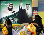 In this Wednesday, Feb. 5, 2020, photo, women carry their shopping bags past a banner showing Saudi King Salman and his Crown Prince Mohammed bin Salman, left, outside a mall in Jiddah, Saudi Arabia. Human rights organization Amnesty International says Saudi Arabia has used a special anti-terrorism court as