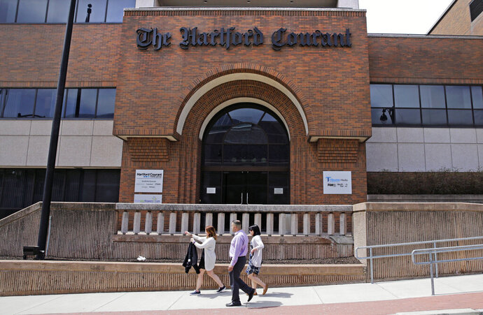 In this April 25, 2016 file photo, workers walk past the front entrance of the Hartford Courant building in Hartford, Conn. Hedge fund Alden Global Capital is now the largest shareholder of Tribune Publishing, the company that owns the Hartford Courant,  the Chicago Tribune, Baltimore Sun and New York Daily News. Tribune says Alden, a hedge fund known for layoffs and slashing costs at newspapers it acquires, purchased the 25% stake from former Tribune chairman Michael Ferro. (AP Photo/Charles Krupa, File)