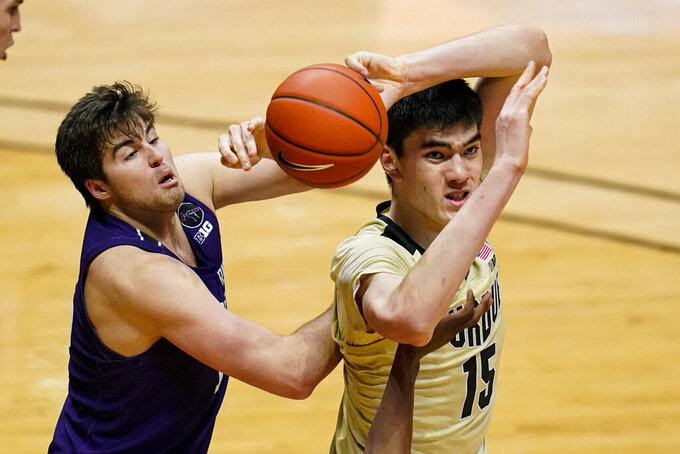 Purdue center Zach Edey, right, loses control of the ball in front of Northwestern center Ryan Young, left, during the second half of an NCAA college basketball game in West Lafayette, Ind., Saturday, Feb. 6, 2021. (AP Photo/Michael Conroy)