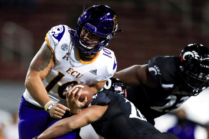 East Carolina quarterback Mason Garcia is tackled by Cincinnati linebacker Deshawn Pace during the second half of an NCAA college football game Friday, Nov. 13, 2020, in Cincinnati. Cincinnati won 55-17. (AP Photo/Aaron Doster)