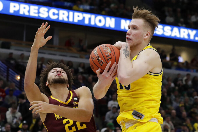 Michigan's Ignas Brazdeikis (13) grabs a rebound against Minnesota's Gabe Kalscheur (22) during the first half of an NCAA college basketball game in the semifinals of the Big Ten Conference tournament, Saturday, March 16, 2019, in Chicago. (AP Photo/Nam Y. Huh)