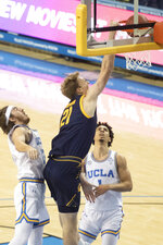 California forward Lars Thiemann, center, slams a dunk past UCLA guard Jake Kyman, left, during the first half of an NCAA college basketball game Sunday, Dec. 6, 2020, in Los Angeles. (AP Photo/Kyusung Gong)