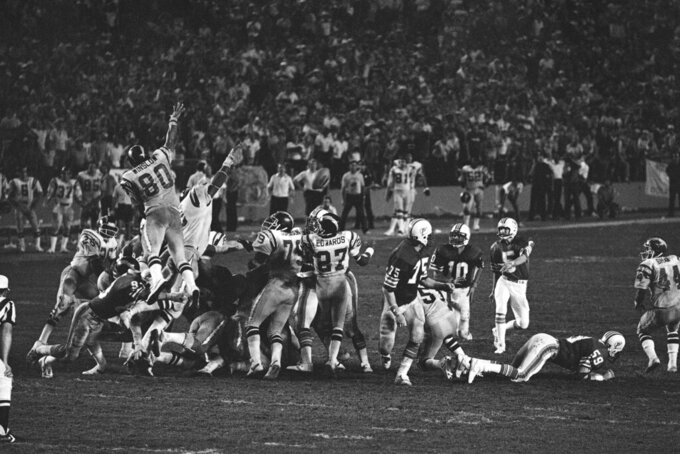 FILE - In this Jan. 2, 1982, file photo, Miami Dolphins kicker Uwe Von Schamann (5) and quarterback Don Strock (10) watch as the ball rebounds from the hands of the defense of the San Diego Chargers as they blocked the Miami Dolphins field goal attempt in overtime of an NFL football AFC playoff game in Miami, Fla. The Chargers won 41-38 on a field goal. (AP Photo/File)