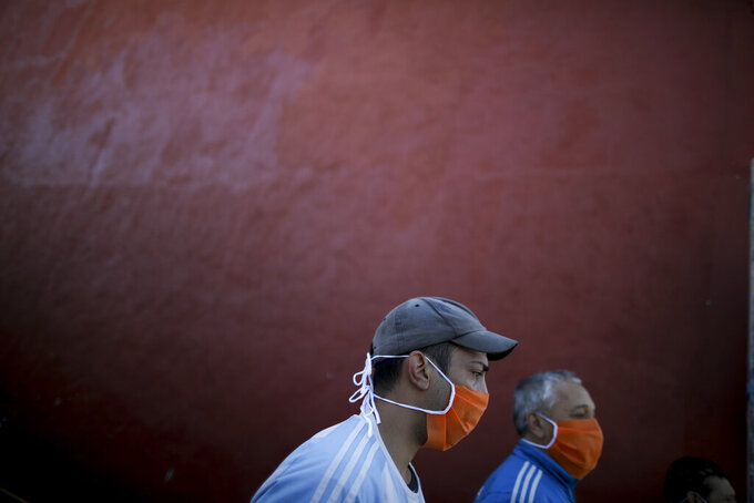 Volunteers at a soup kitchen sing the national anthem with soldiers who delivered the food on the outskirts of Buenos Aires, Argentina, Thursday, April 2, 2020, during a government-ordered lock down to contain the spread of the new coronavirus. (AP Photo/Natacha Pisarenko)