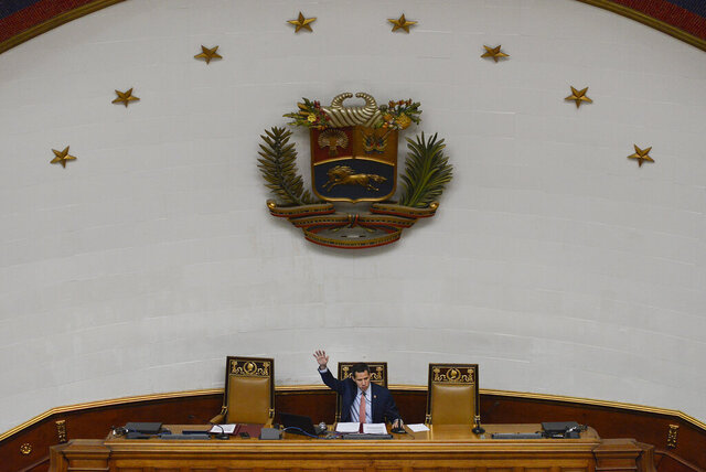 In this Dec. 17, 2019 photo, Venezuelan Opposition leader and self-proclaimed interim president of Venezuela Juan Guaido speaks during an extraordinary session at the National Assembly in Caracas, Venezuela. Cracks have appeared in Guaido's base of support in the National Assembly, the only major institution controlled by the opposition. His reelection as congressional president is no longer assured and legislators' official terms expire in a few months. (AP Photo/Matias Delacroix)