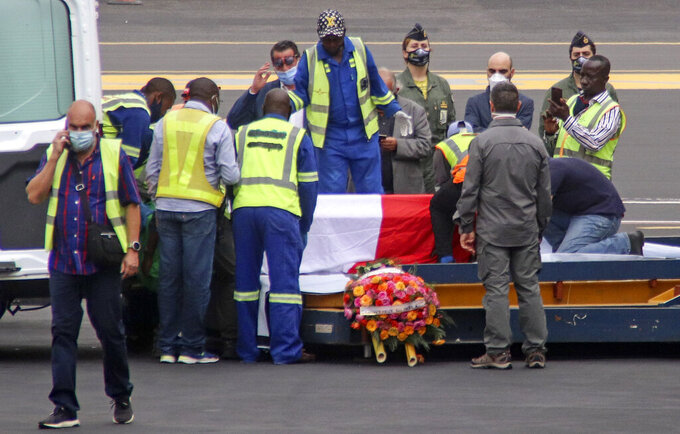 The coffins of Italian ambassador to Congo Luca Attanasio and Carabinieri officer Vittorio Iacovacci, draped with the Italian flag, are prepared to be loaded onto an airplane for repatriation to Italy, at the airport in Goma, North Kivu province, Congo Tuesday, Feb. 23, 2021. An Italian Carabinieri unit is expected in Congo Tuesday to investigate the killings of the Italian ambassador to Congo, an Italian Carabinieri police officer and their driver in the country's east. (AP Photo/Justin Kabumba)