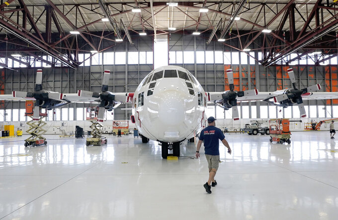 Aircraft Mechanic Cody Poole walks past one of the recently acquired C-130 aircraft, that will be used for firefighting, hangared at the California Department of Forestry and Fire Protection's Sacramento Aviation Management Unit based at McClellan Airpark in Sacramento, Calif., Friday, July 23, 2021. Firefighters are trying to become smarter in how they prepare for the drought- and wind-driven wildfires that have become more dangerous across the American West in recent years, including by adding aircraft like the Sikorsky Firehawk helicopters or military surplus C-130 transport aircraft retrofitted to drop fire retardant. (AP Photo/Rich Pedroncelli)